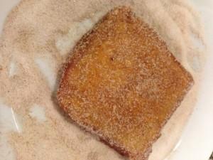 cubriendo torrija con azucar y canela